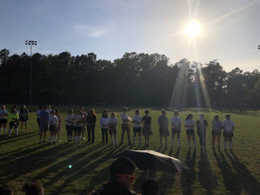 Varsity girls gather for the pledge and the start of their senior game on Wednesday, May 2.