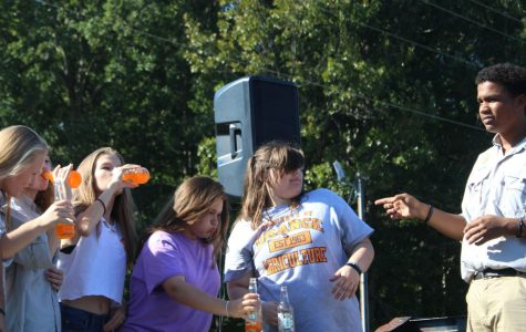 Students drinking a orange crush soda as fast as they can.